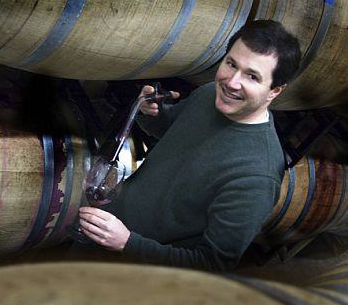 Justin Lattanzio with wineglass and theif around wine barrels