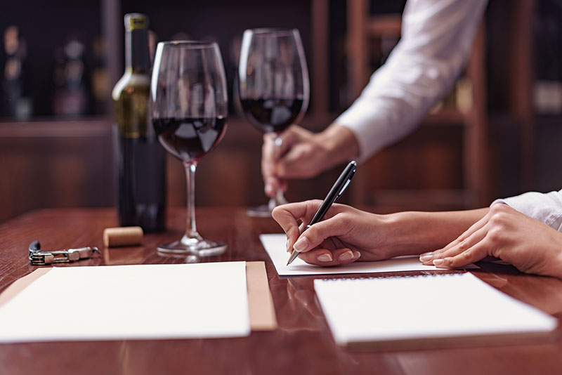 Two people with wine filling out tasting notes.