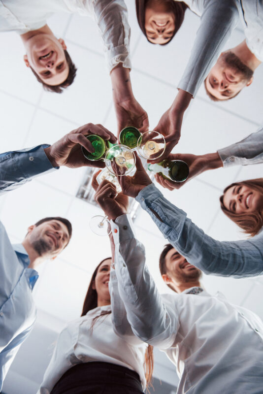 group of people raising a glass of wine